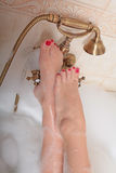 Lady's feet on bath tap Stock Image