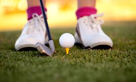 Lady's feet - playing golf at sunset Royalty Free Stock Images