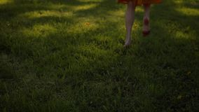 Lady`s feet running by grass in park, barefoot.