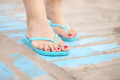 Lady& x27;s feet in sandals on beach Royalty Free Stock Photo