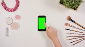 A Finger Touching a Smartphone with a Green Screen. A lady`s finger touching a smartphone with a green screen. The phone is on the white table. View from the top Royalty Free Stock Images