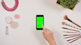 A Finger Touching a Smartphone with a Green Screen. A lady`s finger touching a smartphone with a green screen. The phone is on the white table. View from the top Stock Images