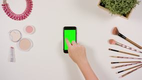 A Finger Touching a Smartphone with a Green Screen. A lady`s finger touching a smartphone with a green screen. The phone is on the white table. View from the top Royalty Free Stock Image