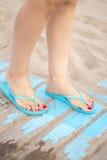 Lady& x27; s-fot i sandaler på stranden Arkivfoton