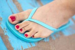 Lady& x27; s-fot i sandaler på stranden Arkivbild