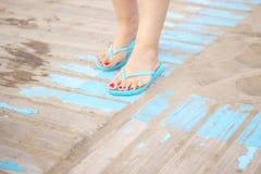 Lady& x27; s-fot i sandaler på stranden Royaltyfri Bild