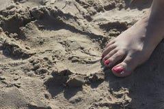 Lady& x27; s-fot i sandaler på stranden Fotografering för Bildbyråer