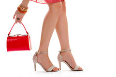 Lady's hand holds red purse. Beige heels and bracelets. Legs of young model. Designer shoes and small accessorries Royalty Free Stock Photography