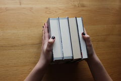 Lady's hands holding books on the table. Young lady's hands holding four books on the wooden table. Student need to learn and read a lot, keeping books Stock Photography