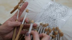 Lady`s hands, making bobbin lace, weaving the bobbins. A woman weaves lace in the old fashion. Handwork. Close-up. A woman weaves lace in the old fashion stock footage