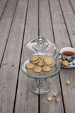 Lady`s Kisses - Italian hazelnut sandwich cookies on cake stand. With cup of tea Royalty Free Stock Photo