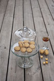 Lady`s Kisses - Italian hazelnut sandwich cookies on cake stand. With a glass of typical Sicilian liqueur Royalty Free Stock Photos
