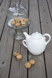 Lady`s Kisses - Italian hazelnut sandwich cookies on cake stand. With White ceramic teapot Royalty Free Stock Image