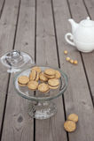 Lady`s Kisses - Italian hazelnut sandwich cookies on cake stand. With White ceramic teapot Royalty Free Stock Photography