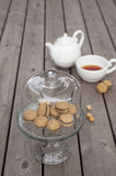 Lady`s Kisses - Italian hazelnut sandwich cookies on cake stand. With White ceramic teapot and cup of tea Royalty Free Stock Image