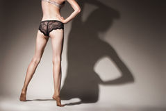 Lady's legs in lingerie against grey background Stock Photography