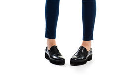 Lady's legs in slip ons. Black glossy footwear. High quality shoes for spring. Durable sole made of rubber Stock Image