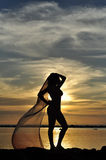 Lady's silhouette at sunset. Lady's silhouette, holding a pareo, at Sunset, at the beach Stock Image