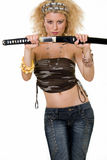 Lady samurai. Attractive woman with wild curly blond hair in a sexy army style tank top shows bare belly holding a samurai sword Royalty Free Stock Photos