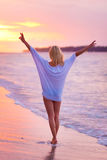 Lady on sandy tropical beach at sunset. stock photos