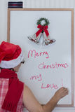 Lady in santa hat writing on white board Stock Photos
