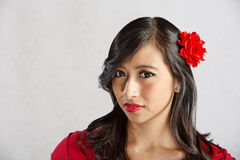 Lady with Sarcastic Grin. Skeptical young Asian woman with sarcastic grin Royalty Free Stock Image