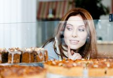 Lady in scarf looking at the bakery window Stock Photography
