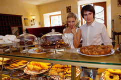 Lady in scarf looking at the bakery window Different pieces of cakes Stock Images