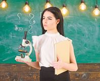 Lady scientist holds book and microscope, chalkboard on background, copy space. Lady in formal wear on calm face in
