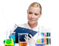 Lady scientist makes some notes. After the experiment, isolated on white stock photography