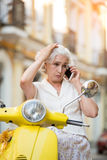 Lady on scooter with phone. Royalty Free Stock Photography