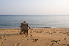 Lady and sea. Lady sits on a chair at the sea in the autumn evening Stock Photo