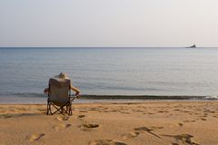 Lady.sea.beacon. Lady sits on a chair at the sea in the autumn evening.Above horizon white overcast Royalty Free Stock Image