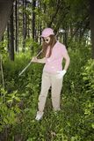 Lady Searching For Lost Golf Ball. A lady golfer searches for her lost ball in the out of bounds area of a golf course in Wisconsin Royalty Free Stock Images