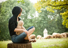 A lady seating. A lady with a bear seating outdoors Royalty Free Stock Photos