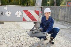 Lady securing balancing foot crane. Lady securing balancing foot of crane Stock Images