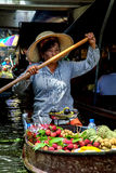 Lady selling fruit from her boat at Floating Market, Stock Photo