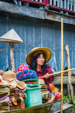 Lady selling hats from her boat at Floating Market, royalty free stock photo