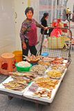 An elderly Asian lady selling various types of dried fish