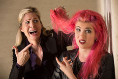 Lady Shocked About Hairdo. Shocked blond women holding pink hairdo of teenager royalty free stock photography
