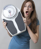 Lady shocked by her weight on the scales. Healthcare concept - surprise in kilos or pounds control for amazed young woman royalty free stock photos