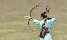 Lady shooting an arrow during World Nomad Games in Kyrgyzstan royalty free stock image
