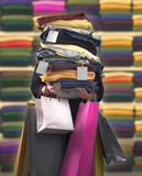 Lady shopper. Woman carrying bags and a pile of clothes with tags royalty free stock photography