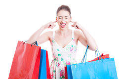 Lady shopper screaming or yelling with ears covered Royalty Free Stock Image