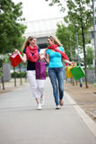 Lady Shoppers Chatting As They Walk Stock Images
