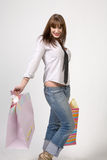 Lady with shopping bags. Cute girl with shopping bags and grey background Royalty Free Stock Photography