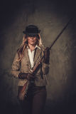 Lady with shotgun and hat from wild west on dark background. Royalty Free Stock Photos