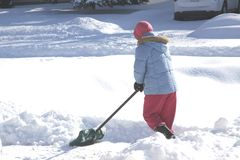 Woman with Shovel in The Snow. Lady with shovel in the deep snow covering Royalty Free Stock Image