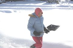 Woman with Shovel in The Snow. Lady with shovel in the deep snow covering Stock Photography
