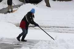 Lady Shoveling Snow from Driveway Stock Photography